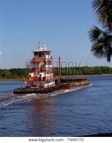 Tugboat pushing barge down river