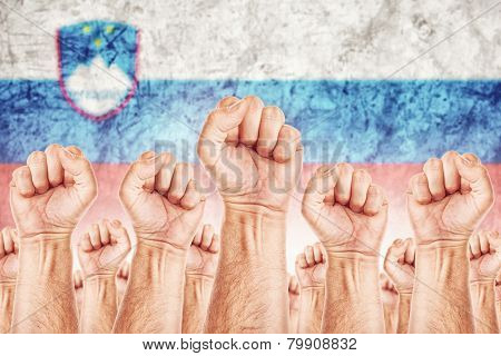 Slovenia Labour movement workers union strike concept with male fists raised in the air fighting for their rights Slovenian national flag in out of focus background. poster