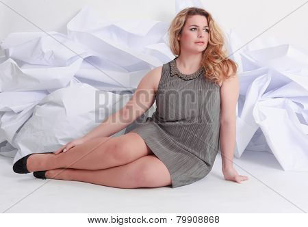 Size Full length portrait of a beautiful plus curly young blond woman posing on white in gray dress and pumps. poster
