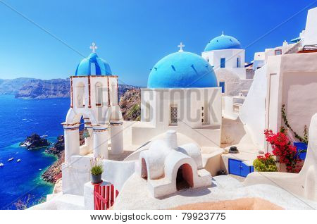 Oia town on Santorini island, Greece. Traditional and famous white houses and churches with blue domes over the Caldera, Aegean sea poster