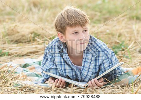 Teenage boy dreaming reading book