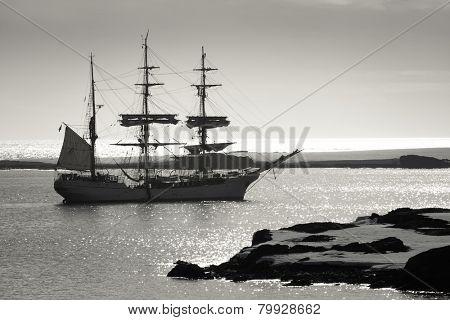 Sailing ship at dawn among the icebergs in Antarctica