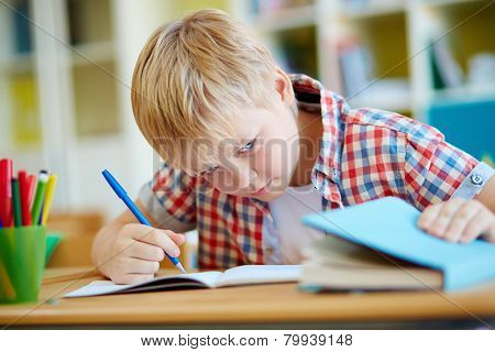 Dishonest schoolboy looking the right answer in book during test