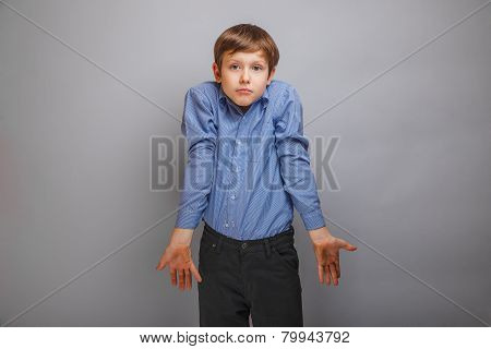 teenager boy in a shirt shrugs