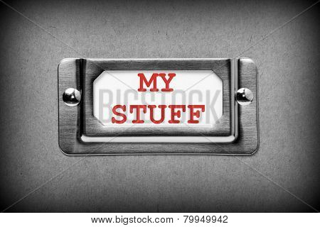A black and white image of a metal drawer label holder with a white index card and the title My Stuff added in red text poster