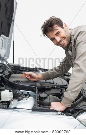 Man using dipstick to check oil in his car
