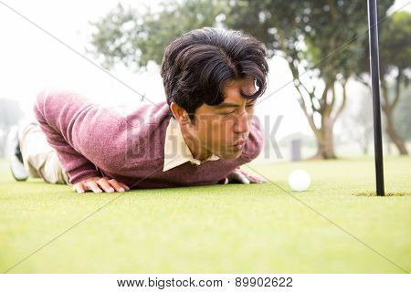 Golfer trying to flick ball into hole at the golf course