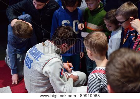 ST. PETERSBURG, RUSSIA - MAY 2, 2015: Winner of the International fencing tournament St. Petersburg Foil Dmitry Rigin of Russia gives autographs to children. The tournament is the stage of World Cup