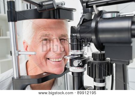 Portrait of happy senior patient using slit lamp at clinic