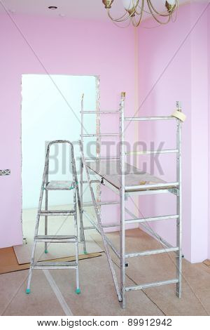Ladder and scaffolding in repaired room with pink walls