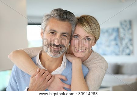 Smiling middle-aged couple standing in brand new home