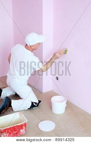 Man in white clothes covers the walls pink decorative plaster