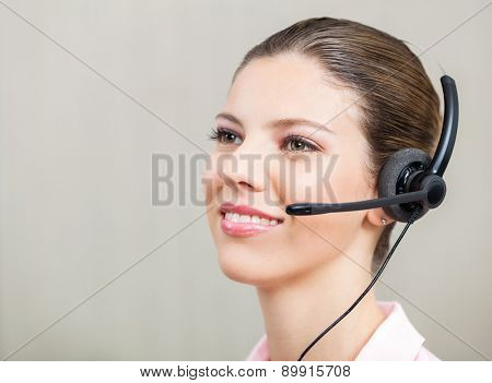 Closeup of customer service representative wearing headphones at office
