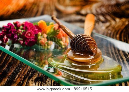 golden honey on plate and colorful flowers