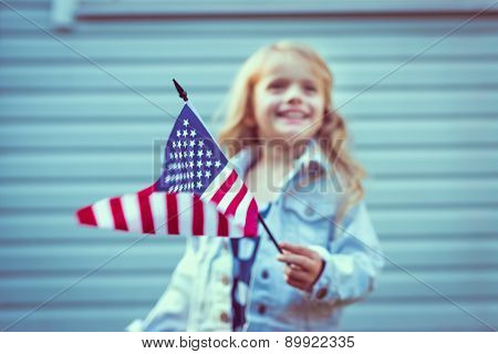 Flying American Flag In Little Girl's Hand. Selective Focus, Blurred Background. Independence Day