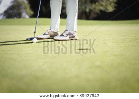 Close up of female golf player putting on green, with empty copyspace, background for text.