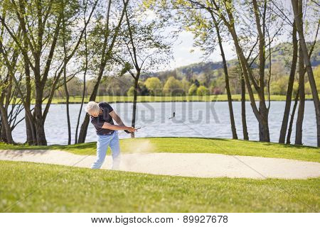 Senior golf player hitting ball in bunker, with lake and trees in background.
