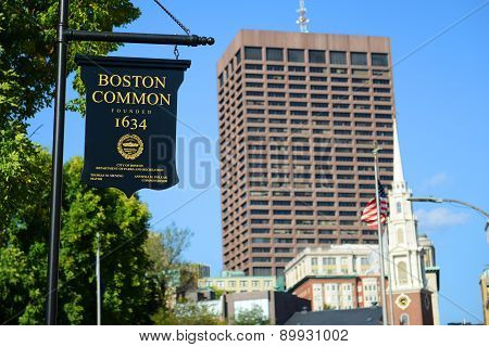 BOSTON - OCT 2, 2013: Sign of Boston Common, with the Park Street Church and Boston skyline on the background in Boston, Massachusetts, USA.
