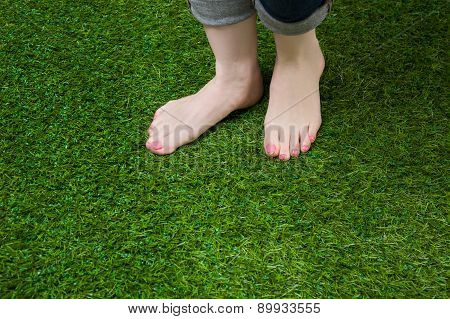 Woman legs in jeans stepping on grass