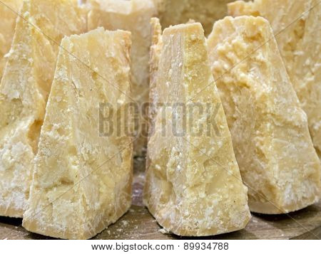 Thick Slices Of Italian Parmesan Cheese On  Wooden Cutting Board