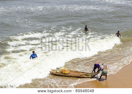 Unidentified Fishermen Land With A Bamboo Boat And The Net At The Beach
