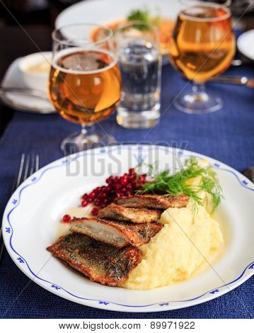Traditional Swedish dish with fried herring and mashed potatoes and lingon berries served with beer