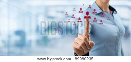 Human resources CRM and social networking concept - female officer choose person (employee) represented by icon. Out of focused office in background wide composition. poster