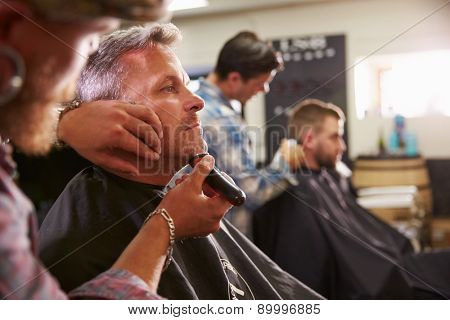 Male Barber Giving Client Shave In Shop