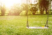 Abandoned swing in warm sunny light with flowers in the spring season poster