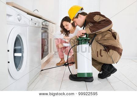Worker Spraying Insecticides In Front Of Housewife
