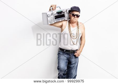 Senior man in a hip-hop outfit carrying ghetto blaster over his shoulder and looking at the camera