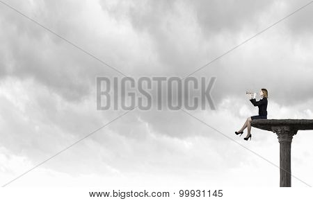 Young businesswoman sitting on top and proclaiming something in horn