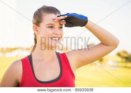 Smiling sporty blonde looking far away at promenade