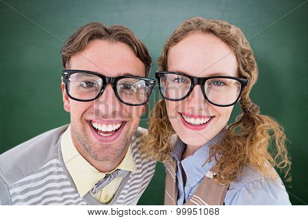 Happy geeky hipster smiling at camera against green chalkboard