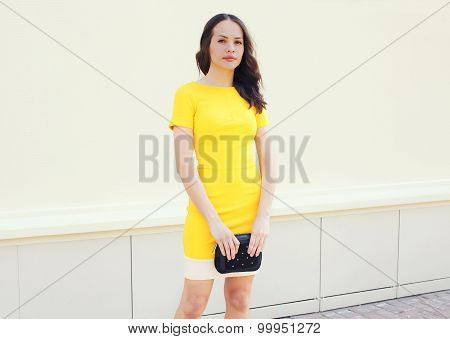Beautiful young woman in yellow dress with black handbag clutch over white background poster