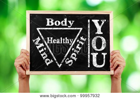 Hands holding blackboard with text You Body Spirit Soul Mind Healthy against green blurred background. poster