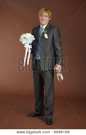 Groom With Bouquet And Bottle Of Sparkling Wine
