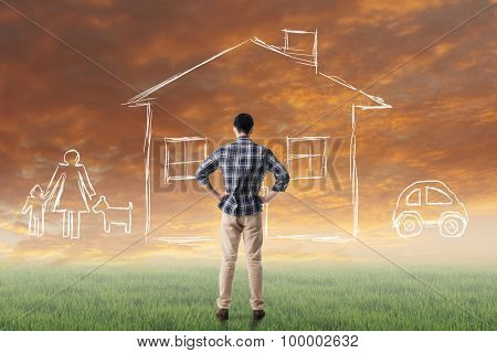 Asian man look toward the drawing house and family in the heaven.