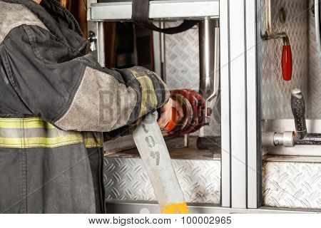Midsection side view of fireman adjusting water hose in truck at fire station