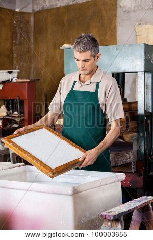 Mature male worker holding mold over pulp and water mixture at paper factory