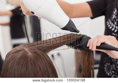 Skilled young hairdresser is using a hairdryer in beauty shop