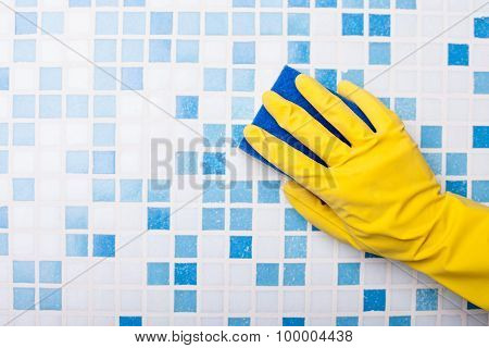 Skilled swabber is cleaning wall with a sponge