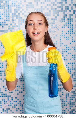 Attractive young cleaner is dusting her house
