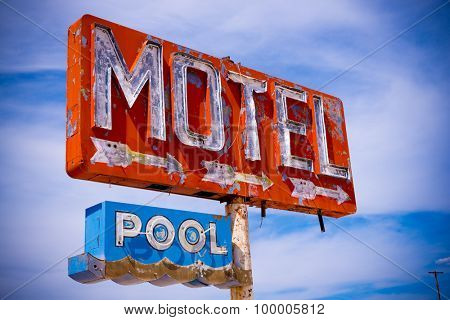 An old, flaking neon motel sign in the American Desert.  Abandoned signage.