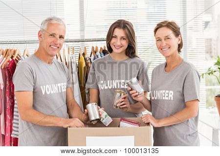 Portrait of smiling volunteers sorting donations in the office
