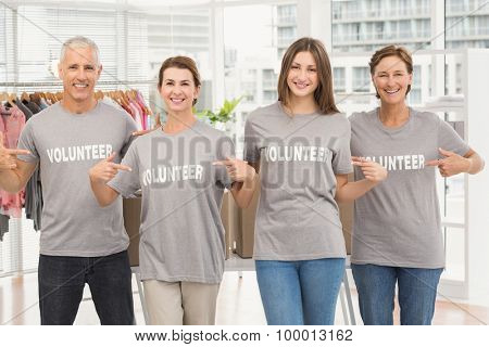 Portrait of smiling volunteers pointing on their shirts in the office