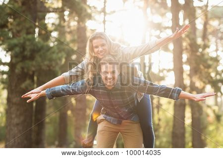 Portrait of smiling handsome man giving piggy back to his girlfriend in the nature