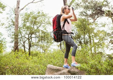 Blonde hiker looking through binoculars in the nature