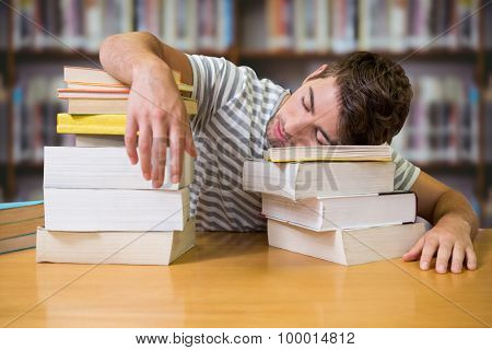 Student asleep in the library against books on desk in library