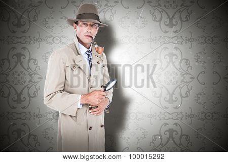 Spy looking through magnifier against elegant patterned wallpaper in grey tones